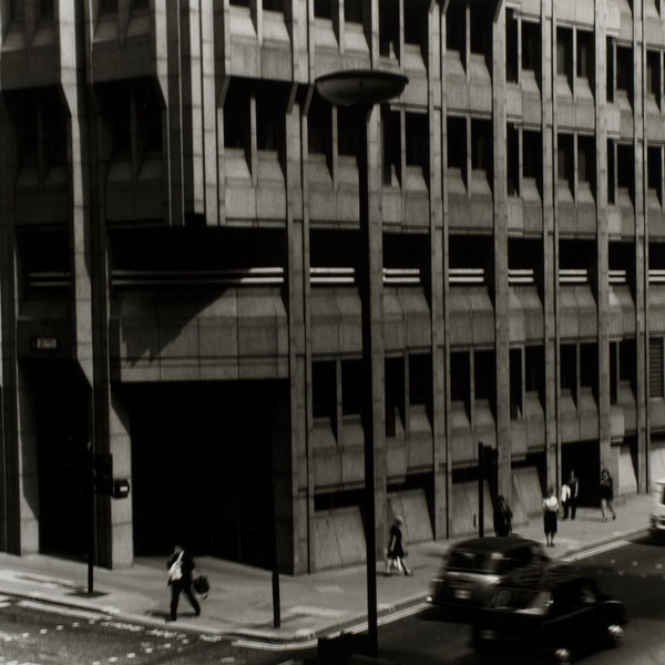 Figures passing a building