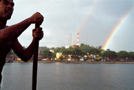Fisherman in Brazil paddling with double rainbow.